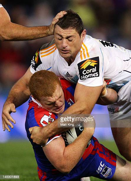 Alex McKinnon of the Knights is tackled by Mark Minichiello of the Titans during the round 12 NRL match between the Newcastle Knights and the Gold...