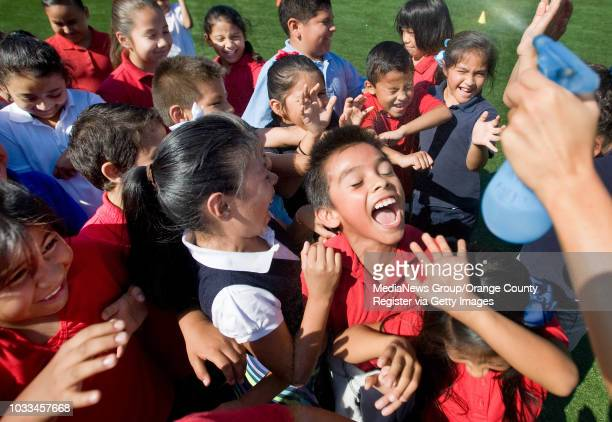 Alex MerinoCruz center enjoys a cool spray of water while on the playground with classmates at Garfield Elementary School in Santa Ana on Wednesday...
