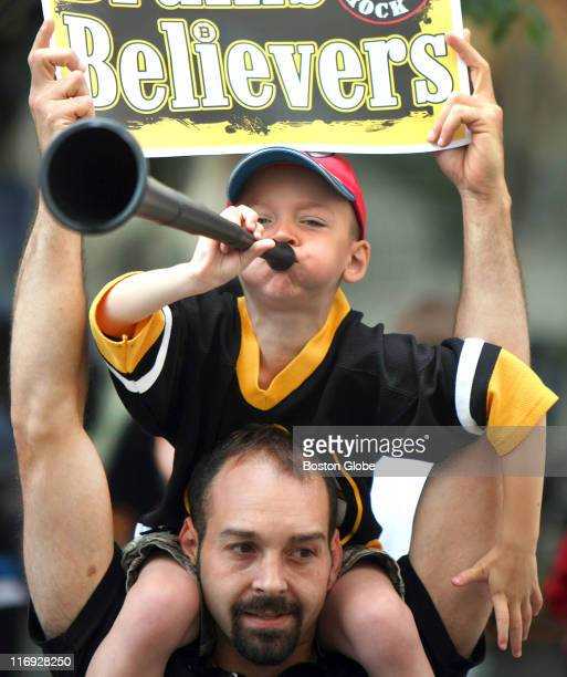 Alex Merloni 5 from North Grafton blows a horn He is sitting on his dad Gregg's shoulders on Boylston Street for the Bruins victory parade