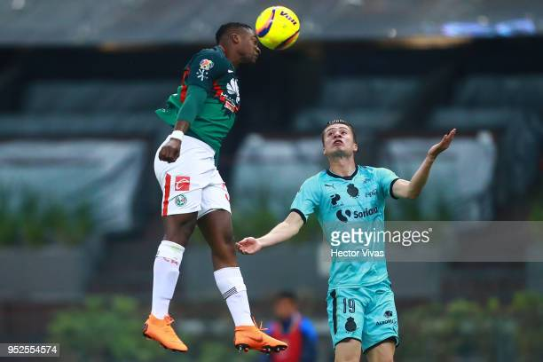 Alex Mina of America heads the ball over the mark of Jorge Flores of Santos Laguna during the 17th round match between America and Santos Laguna as...