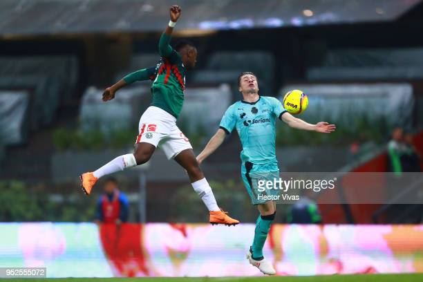 Alex Mina of America jumps for the ball with Jorge Flores of Santos Laguna during the 17th round match between America and Santos Laguna as part of...