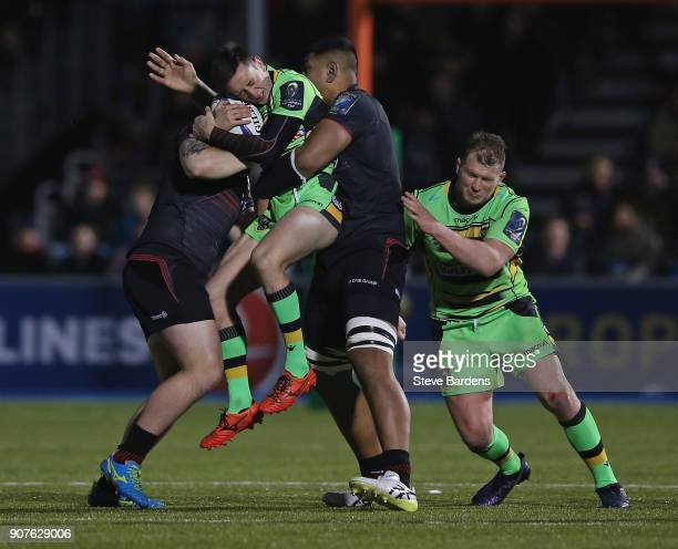 Alex Mitchell of Northampton Saints is held off the ground by the tackles of Hayden ThompsonStringer and Will Skelton of Saracens during the European...
