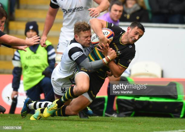 Alex Mitchell of Northampton Saints is tackled by Ian Madigan of Bristol Bears as he scores a try during the Premiership Rugby Cup match between...