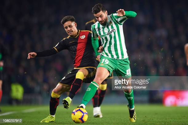 Alex Moreno of Rayo Vallecano competes for the ball with Antonio Barragan of Real Betis Balompie during the La Liga match between Real Betis Balompie...