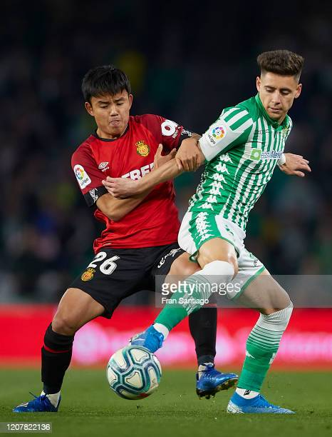 Alex Moreno of Real Betis competes for the ball with Takefusa Kubo of RCD Mallorca during the Liga match between Real Betis Balompie and RCD Mallorca...