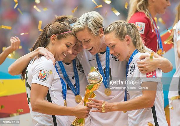 Alex Morgan , Lauren Holiday, Abby Wambach, and Whitney Engen of team USA celebrate with the World Cup trophy after their victory during 2015 women's...