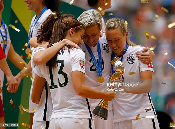 Alex Morgan, Lauren Holiday, Abby Wambach and Whitney Engen of the United States of America hold the World Cup Trophy after their 5-2 win over Japan...