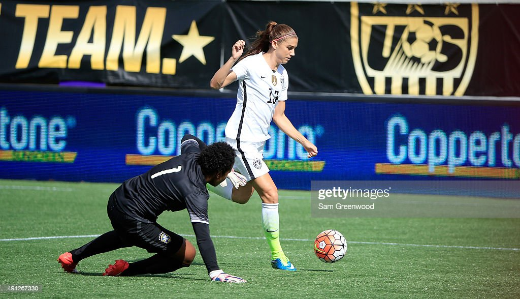 Alex Morgan #13 of the United States drives against Luciana of Brazil for a goal during a Women's International Friendly soccer match at Orlando Citrus Bowl on October 25, 2015 in Orlando, Florida.