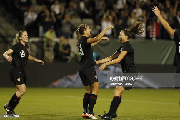 Alex Morgan of the United States is hoisted by Lauren Cheney after scoing a goal against Canada on September 22 2011 at JeldWen Field in Portland...