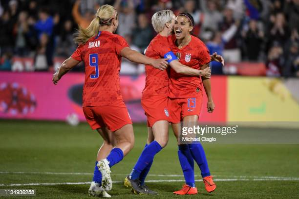 Alex Morgan of the United States, right, celebrates with Megan Rapinoe, center, and Lindsey Horan, left, after scoring her 100th international goal...