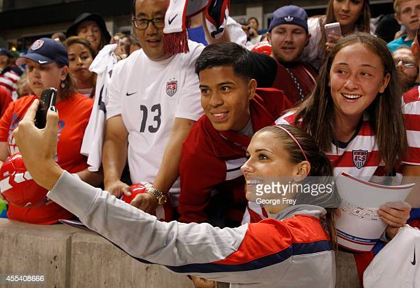 Alex Morgan of the United States takes a selfie shot with fans after a game against Mexico at an international friendly soccer game September 13,...