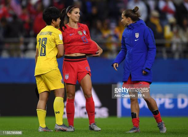 Alex Morgan of the USA collects the match ball as she celebrates victory while speaking to Sukanya Chor Charoenying of Thailand during the 2019 FIFA...