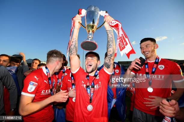 Alex Mowatt of Barnsley celebrates with the second place trophy after getting promoted following the Sky Bet League One match between Bristol Rovers...