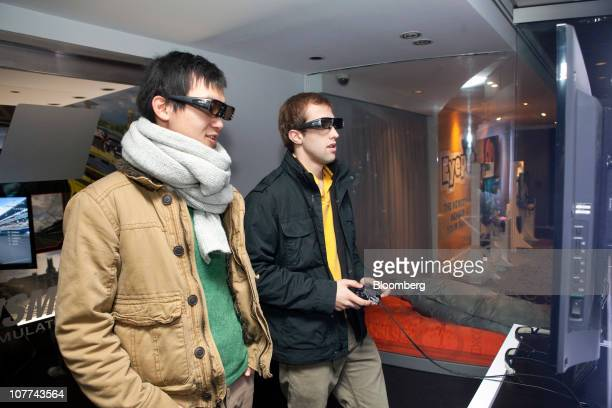 Alex Munoz right and a friend wear 3D glasses while playing a game on a Sony Corp Playstation 3 video game system at the Sony Style Store in New York...