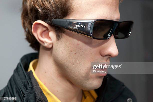 Alex Munoz wears 3D glasses while playing a game on a Sony Corp Playstation 3 video game system at the Sony Style Store in New York US as the...