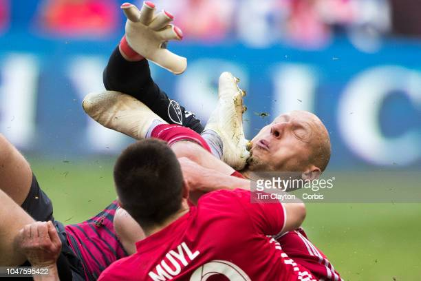 Alex Muyl of New York Red Bulls challenges Brad Guzan of Atlanta United who takes a boot to the face as he challenges for the ball which resulted in...