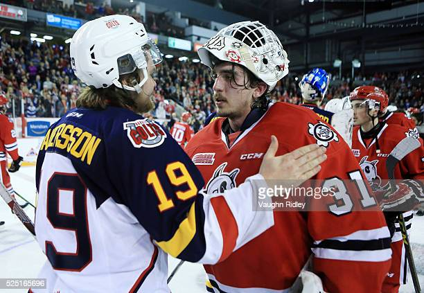 Alex Nedeljkovic of the Niagara IceDogs is congratulated by Rasmus Andersson of the Barrie Colts following Game Four of the 2016 OHL Eastern...