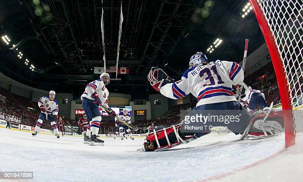 Alex Nedeljkovic of the USA National Junior Team makes a glove save against the Massachusetts Minutemen as teammates Kieffer Bellows and Chad Krys...