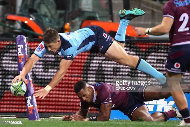 TOPSHOT Alex Newsome of the NSW Waratahs dives over Filipo Daugunu from the Queensland Reds but fails to score a try during the Super Rugby match at...