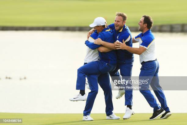 Alex Noren of Europe celebrates winning his match on the 18th green with team mates Thorbjorn Olesen Tyrrell Hatton and Francesco Molinari of Europe...