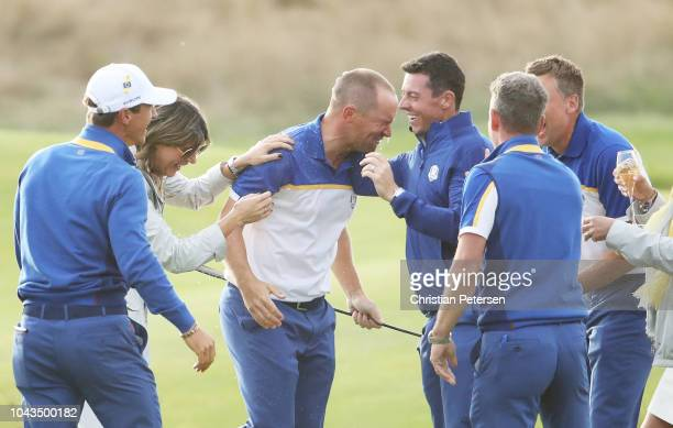 Alex Noren of Europe celebrates with Team Europe after winning his match on the 18th green as Europe win The Ryder Cup during singles matches of the...
