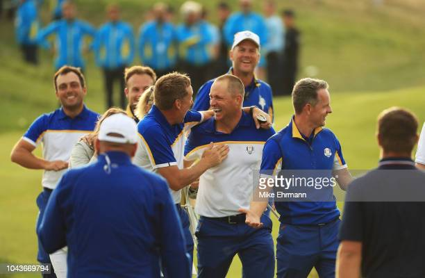 Alex Noren of Europe celebrates with team mates on the 19th green following winning The Ryder Cup during singles matches of the 2018 Ryder Cup at Le...