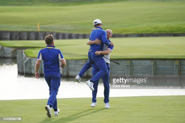 Alex Noren of Europe is congratulated by Rory McIlroy of Europe and Tyrrell Hatton of Europe after he wins his match in the Singles during Day Three...