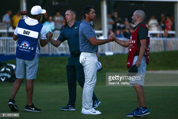 Alex Noren of Sweden and Jason Day of Australia shake hands with caddies after play was suspend due to darkness after five playoff holes during the...