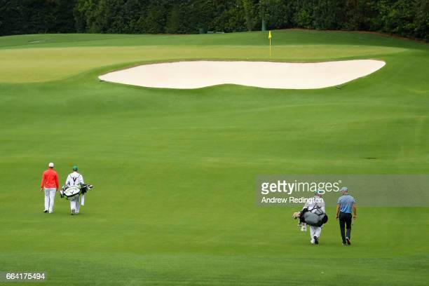 Alex Noren of Sweden and Martin Kaymer of Germany walk down the fourth hole with their caddies during a practice round prior to the start of the 2017...
