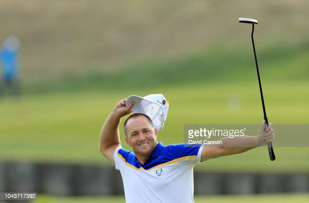 Alex Noren of Sweden and the European Team celebrates after holing a putt on the 18th green to win his match against Bryson de Chambeau of the United...