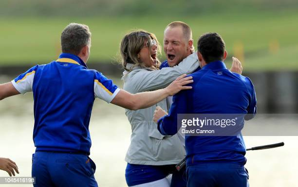 Alex Noren of Sweden and the European Team is embraced by his wife Jennife Kovacs after he had holed a huge putt on the 18th green to win his match...