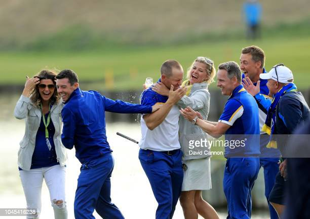 Alex Noren of Sweden and the European Team is embraced by teammates after he had holed a huge putt on the 18th green to win his match against Bryson...