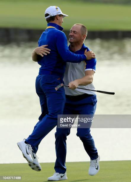 Alex Noren of Sweden and the European Team is embraced by Thorbjorn Olesen after Noren had holed a long putt on the 18th green to win his match...