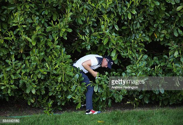Alex Noren of Sweden emerges from the bushes on the 18th hole during day one of the BMW PGA Championship at Wentworth on May 26 2016 in Virginia...