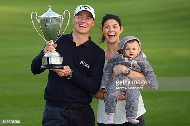 Alex Noren of Sweden his girlfriend Jennifer Kovacs and their daughter Iris pose with the trophy following his victory during the fourth round of the...