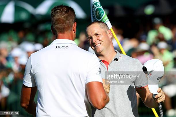 Alex Noren of Sweden is congratulated by Henrik Stenson on the 18th green during day four of the Nedbank Golf Challenge at Gary Player CC on November...