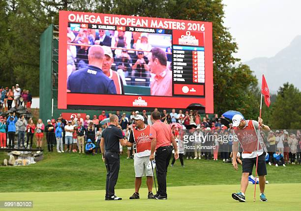 Alex Noren of Sweden is congratulated by Scott Hend following his victory after sinking a long putt on the the first extra hole during the final...