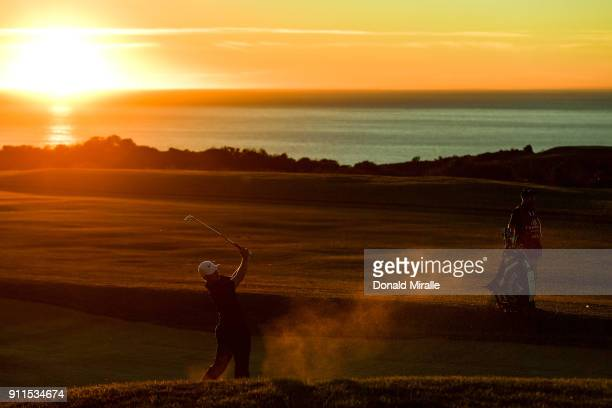 Alex Noren of Sweden plays a shot from a bunker on the 17th hole on the fourth playoff hole during the final round of the Farmers Insurance Open at...
