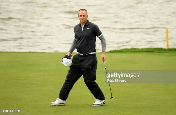 Alex Noren of Sweden re-enacts his Ryder Cup putt on the 18th green during the pro-am event prior to the Amundi Open de France at Golf National on...