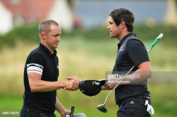 Alex Noren of Sweden shakes hands with Nacho Elvira of Spain after winning their match on hole 17 on day two of the Aberdeen Asset Management Paul...