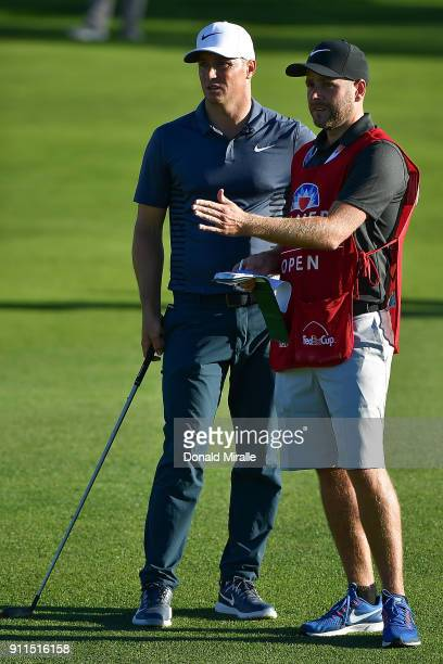 Alex Noren of Sweden talks with his caddie on the 18th hole during the final round of the Farmers Insurance Open at Torrey Pines South on January 28...