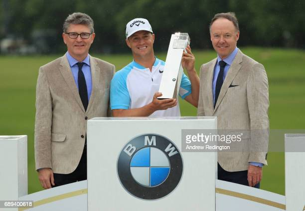 Alex Noren of Sweden with Graeme Grieve and Ian Robertson of BMW with the trophy during day four of the BMW PGA Championship at Wentworth on May 28...