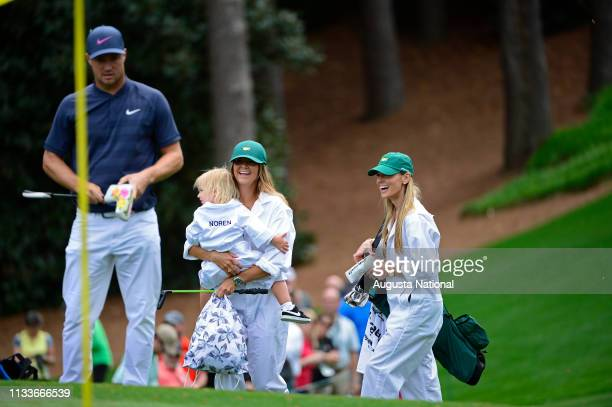 Alex Noren of Sweden's caddie has her hands full as she walks wirth Rory McIlroy of Northern Ireland's caddie during the Par 3 Contest at Augusta...