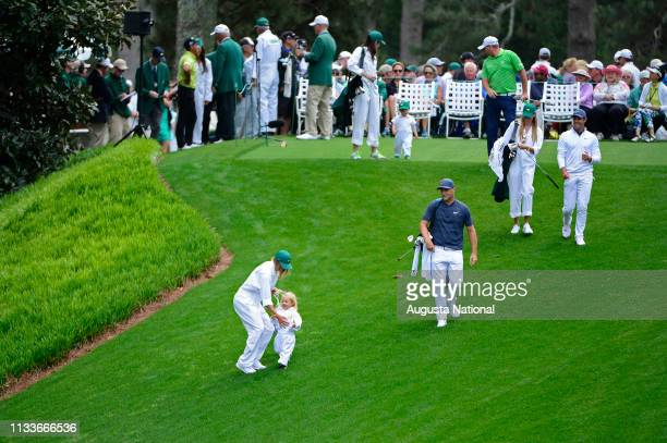 Alex Noren of Sweden's caddie stops an assistant caddie from scrambling downhill on No 1 as they walk with Ted Potter Jr and Rory McIlroy of Northern...