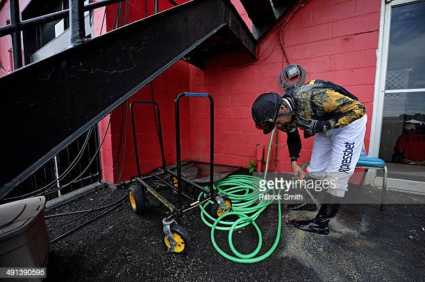 Alex O Solis jockey of Sky Given rinses off after a BlackEyed Susan Day race a day prior to the 139th Preakness Stakes at Pimlico Race Course on May...