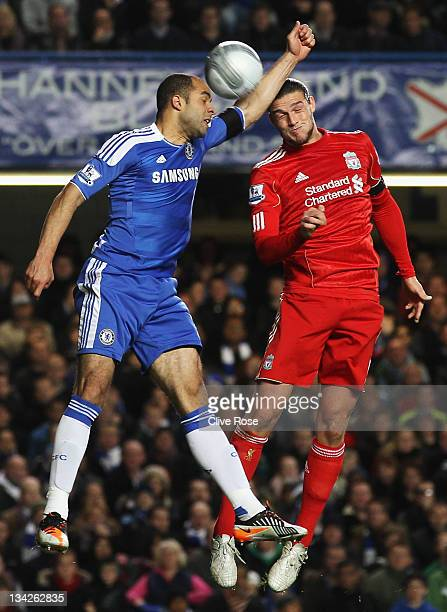 Alex of Chelsea gives away a hand ball leading to a penalty under a challenge by Andy Carroll of Liverpool during the Carling Cup quarter final match...