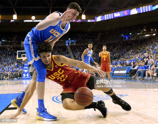 Alex Olesinski of the UCLA Bruins guards Bennie Boatwright of the USC Trojans as he slips driving to the basket in the second half at Pauley Pavilion...