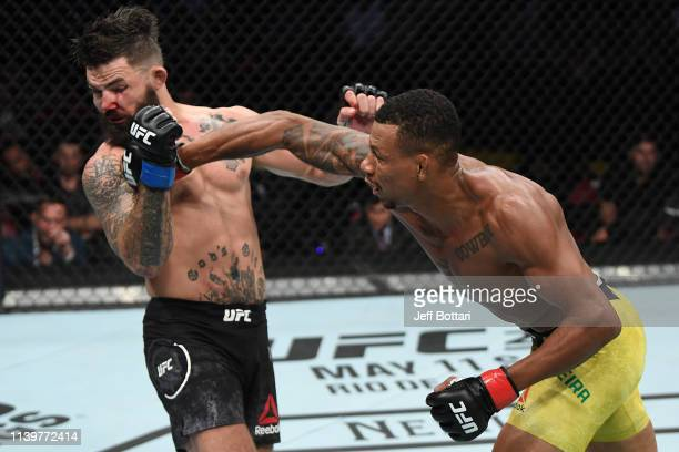 Alex Oliveira of Brazil punches Mike Perry in their welterweight bout during the UFC Fight Night event at BB&T Center on April 27, 2019 in Sunrise,...
