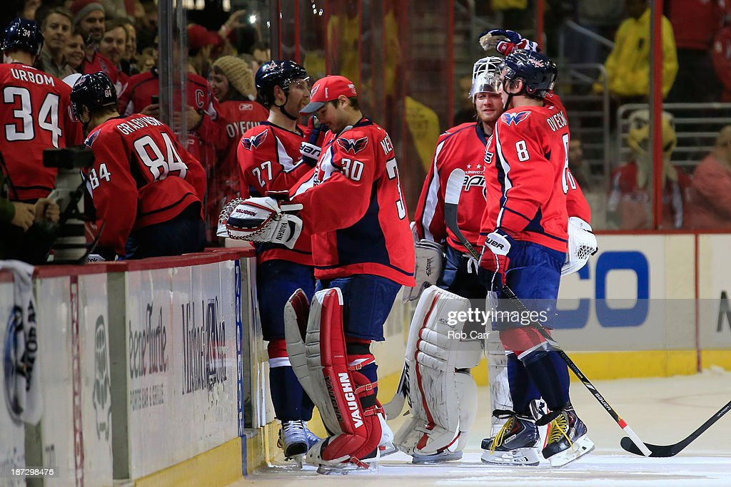 Alex Ovechkin #8 and Braden Holtby #70 of the Washington Capitals celebrate followoing the Capitals 3-2 shootout win over the Minnesota Wild at Verizon Center on November 7, 2013 in Washington, DC.