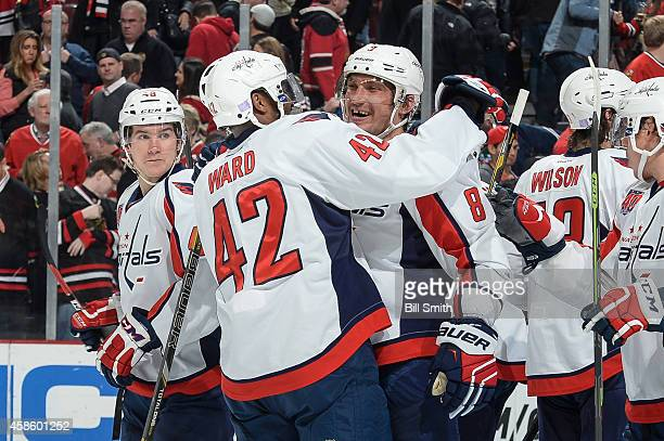 Alex Ovechkin and Joel Ward of the Washington Capitals celebrate as Michael Latta stands to the side after defeating the Chicago Blackhawks 32 during...